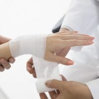 Doctors bandage to women of wrist